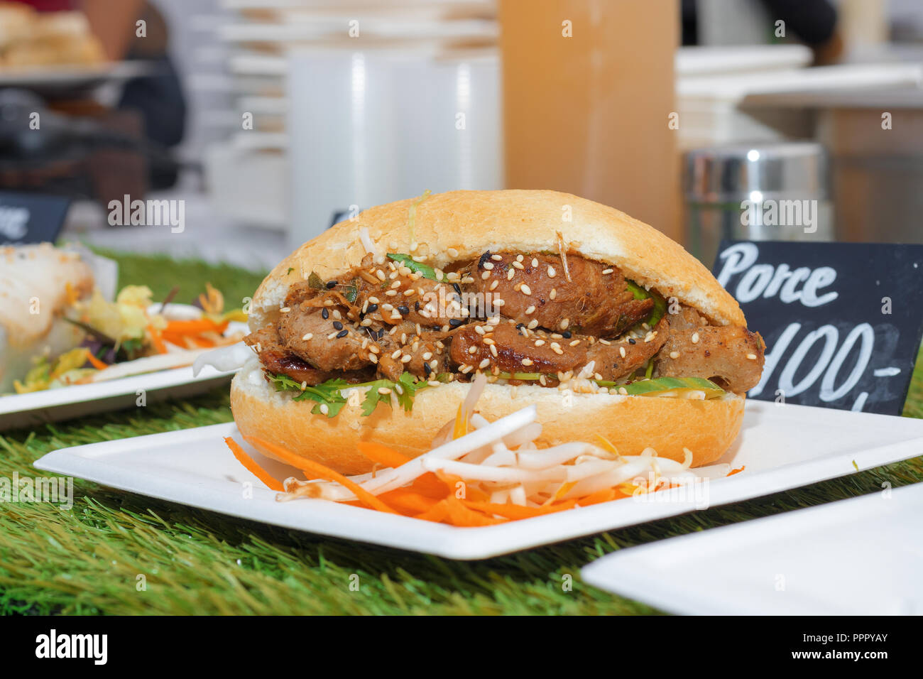 The paper coaster with Vietnamese variation of the burger, bread, lamb meat and the fresh vegetable. - Stock Image