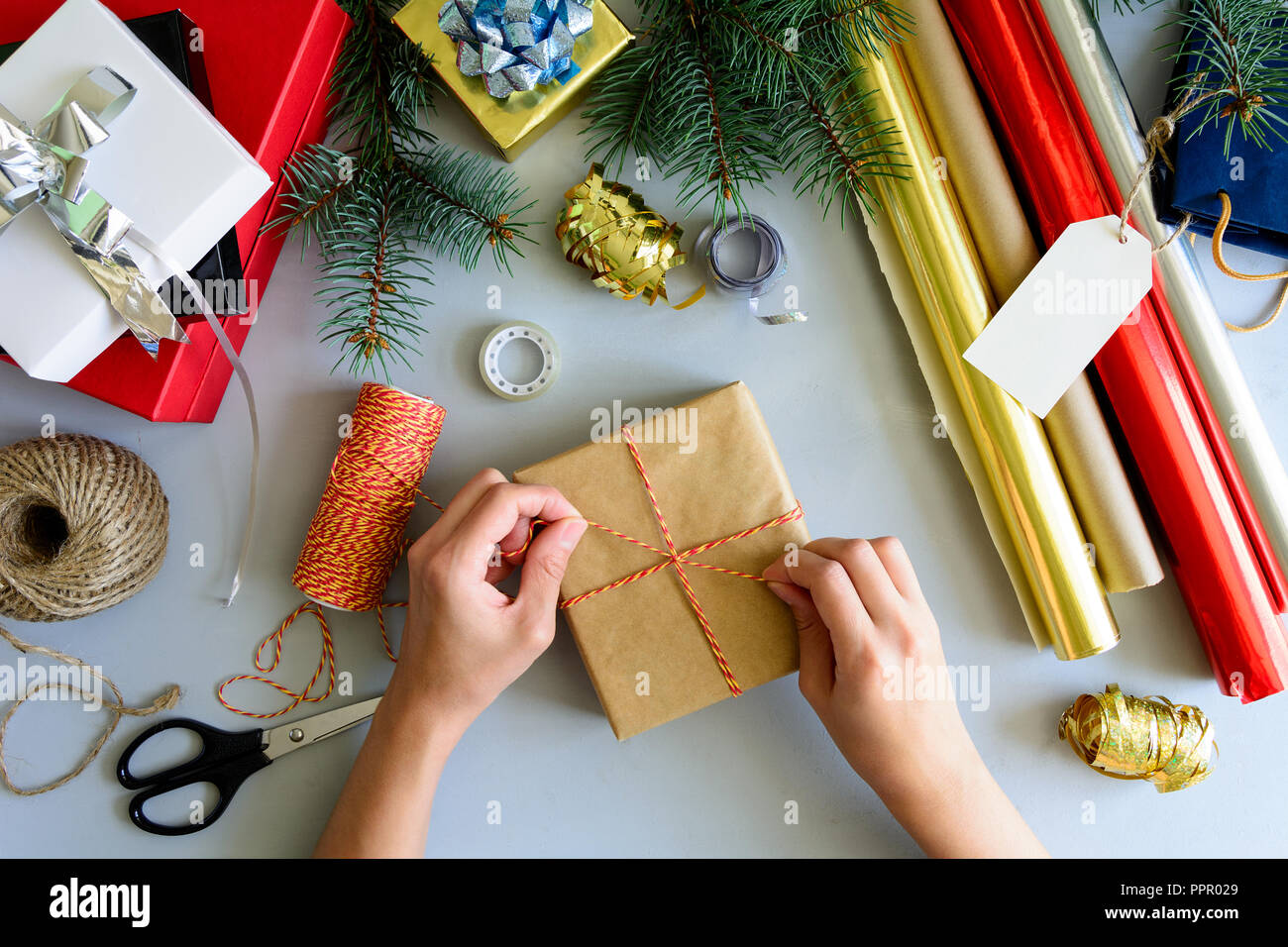 womans hands decorate present box on gray wooden background new year and christmas decorations concept
