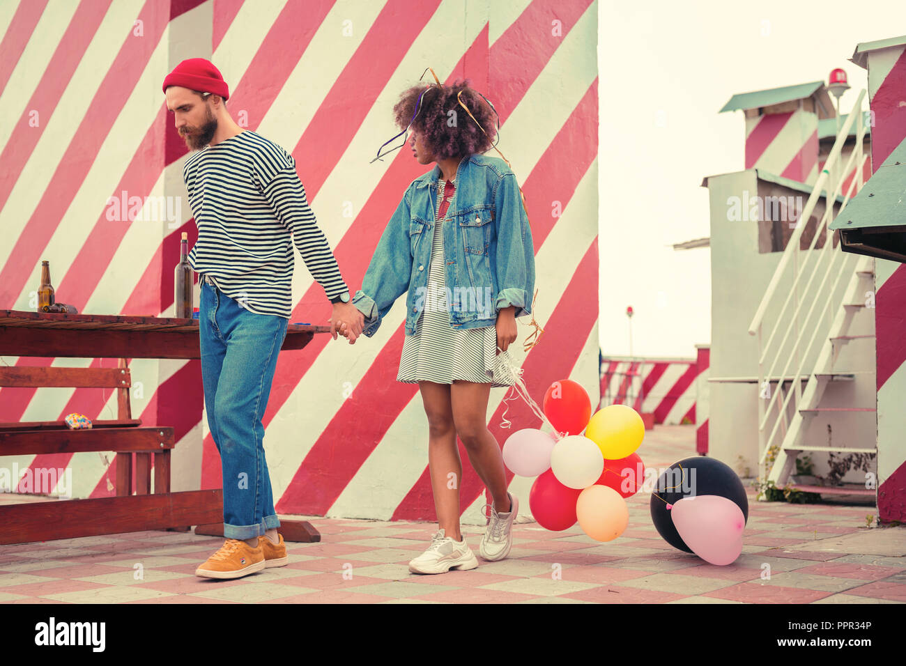 Exhausted couple walking on the roof after night party and looking sleepy - Stock Image
