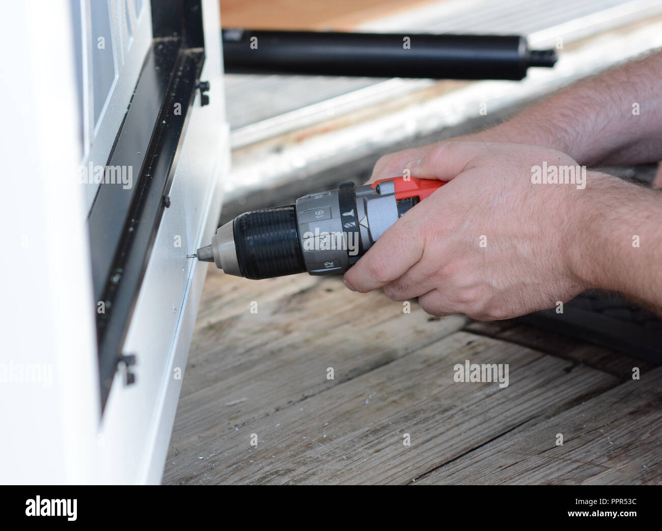 Closeup of a man's hands using a power tool to install a screen door. - Stock Image