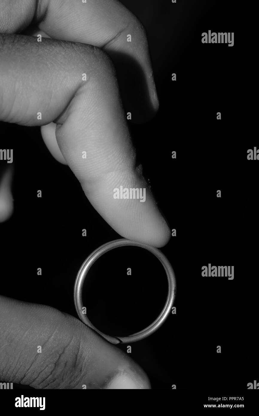 A young married man (adult person) holding with finger in hand one single attractive beautiful shiny polished precious gold platinum diamond silver an Stock Photo