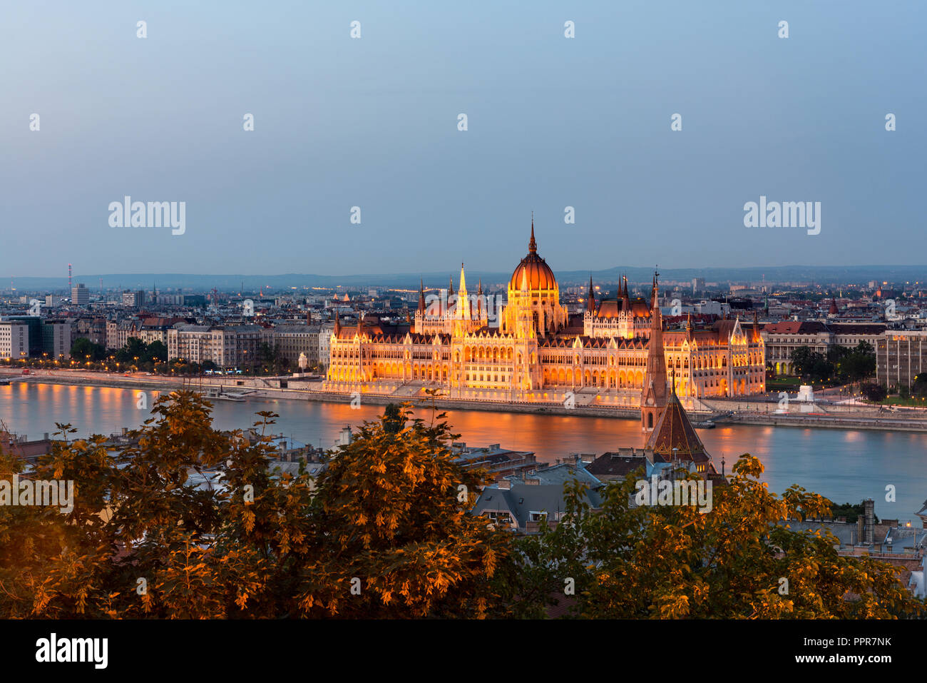 Panorama view of the illuminated Hungarian Parliament across the river Danube at dusk, Budapest. Long exposure. - Stock Image
