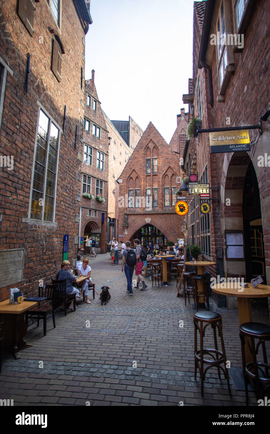 Narrow alley with red brick buildings, cafe and restaurant in Bremen famous Boettcherstrasse - Germany Stock Photo