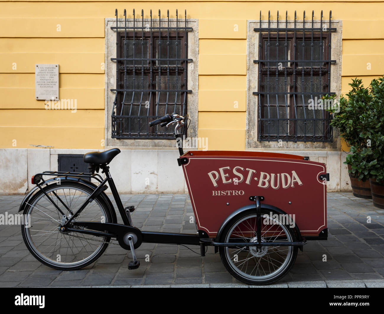 Budapest, Hungary - August 16, 2018: Tricycle advertisement of Pest-Buda bistro in historic city centre of Budapest, Hungary. - Stock Image