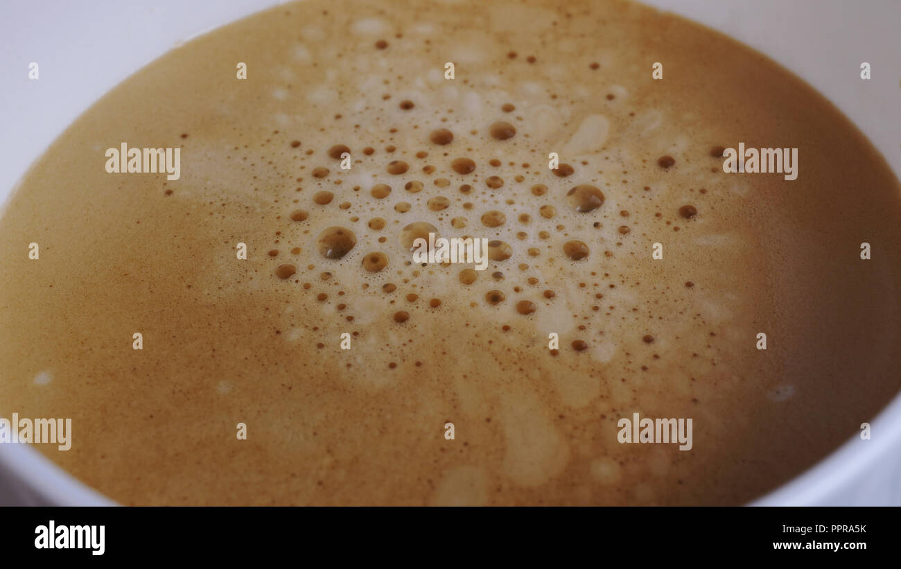 Extremely close up view of white cup. Espresso with bubbles pouring from professional coffee machine. Coffee maker. Modern technology concept - Stock Image