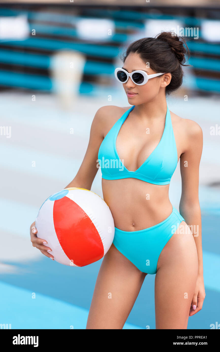 beautiful girl in bikini and sunglasses with inflatable ball at poolside - Stock Image
