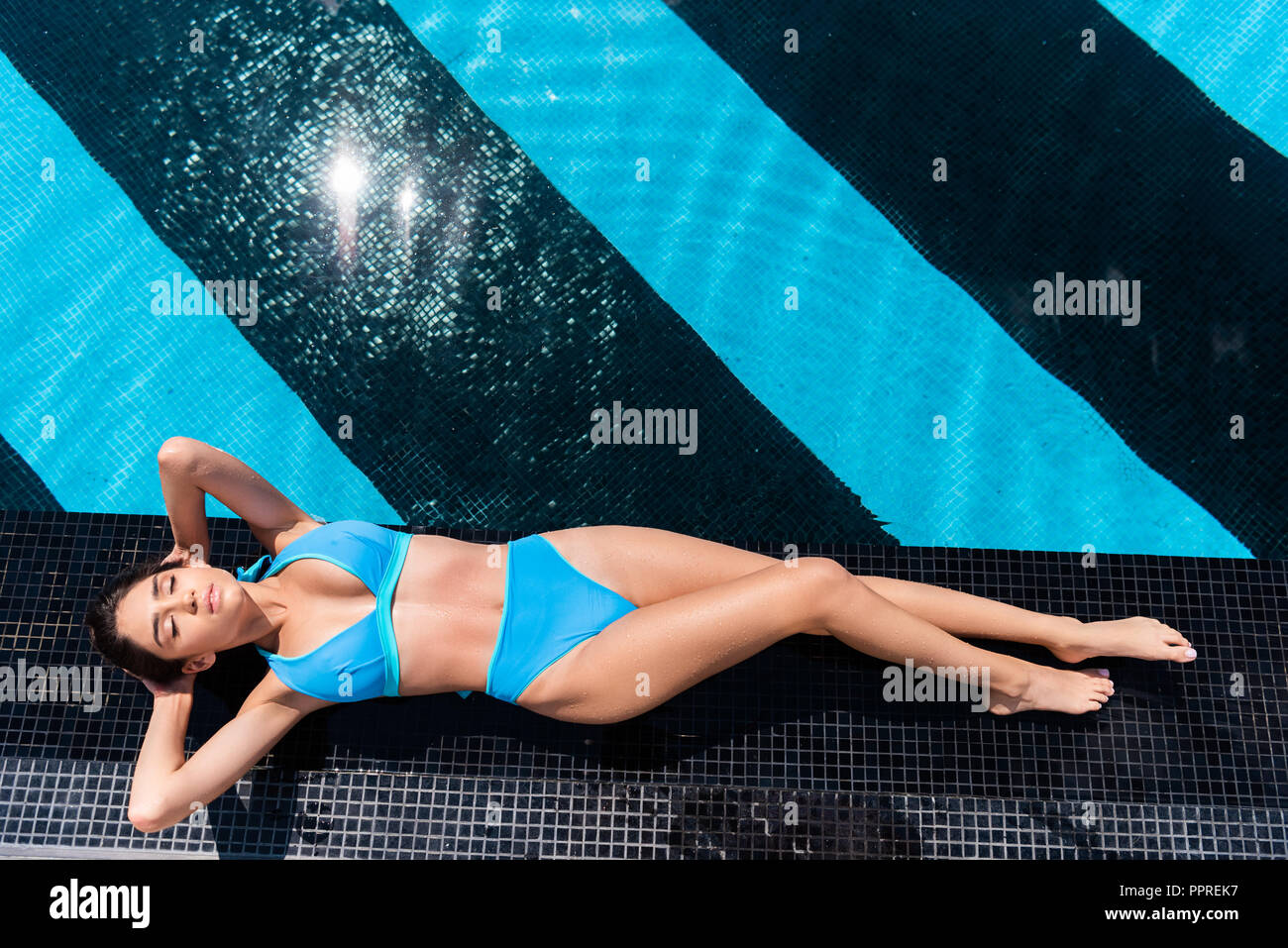 top view of girl in blue bikini sunbathing at poolside - Stock Image