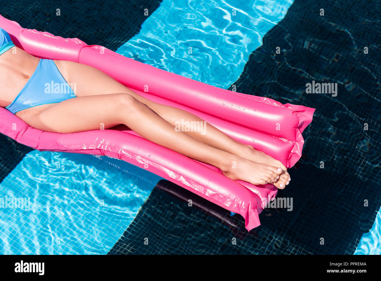low section view of girl resting on pink inflatable mattress in swimming pool - Stock Image