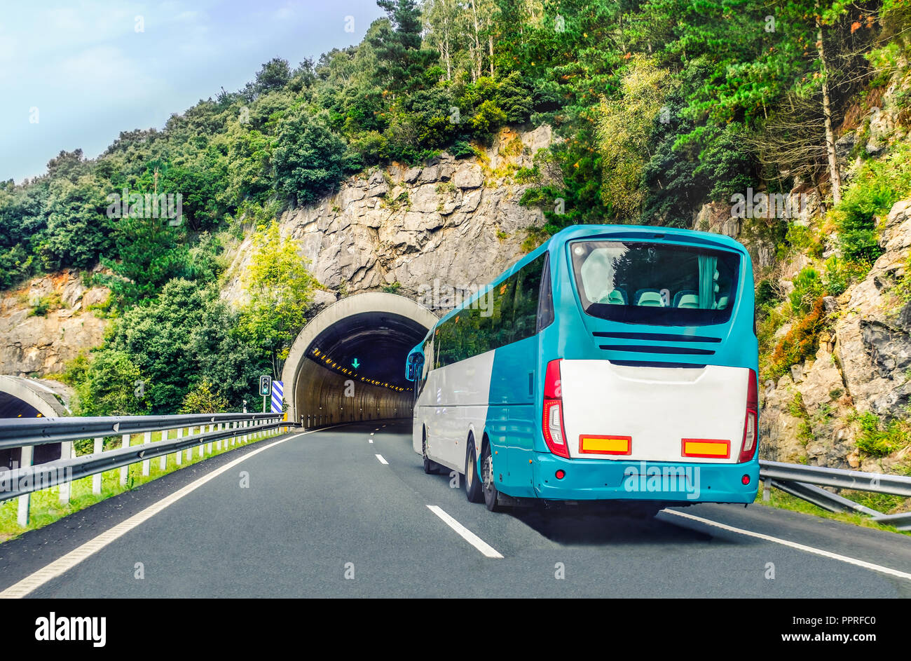 A white and blue coach, or long haul bus for tourists drives through the mountain tunnels and roads of Northern Spain, Europe on a summer day. - Stock Image