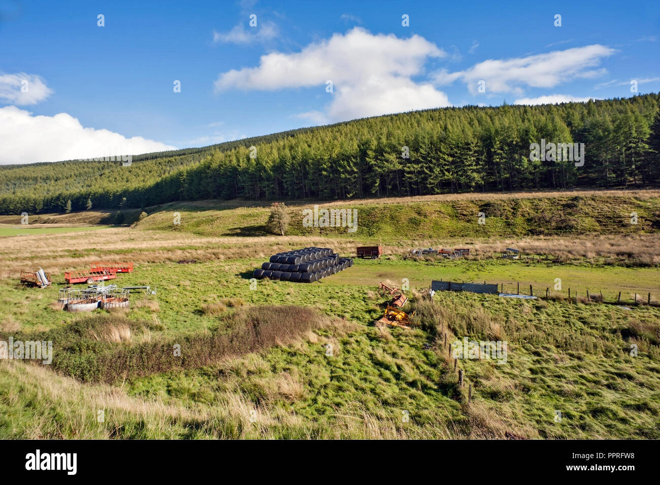 Straw bales and farming equipment  in field on hill farm, September,  Angus, Scotland with conifer forest in background. - Stock Image