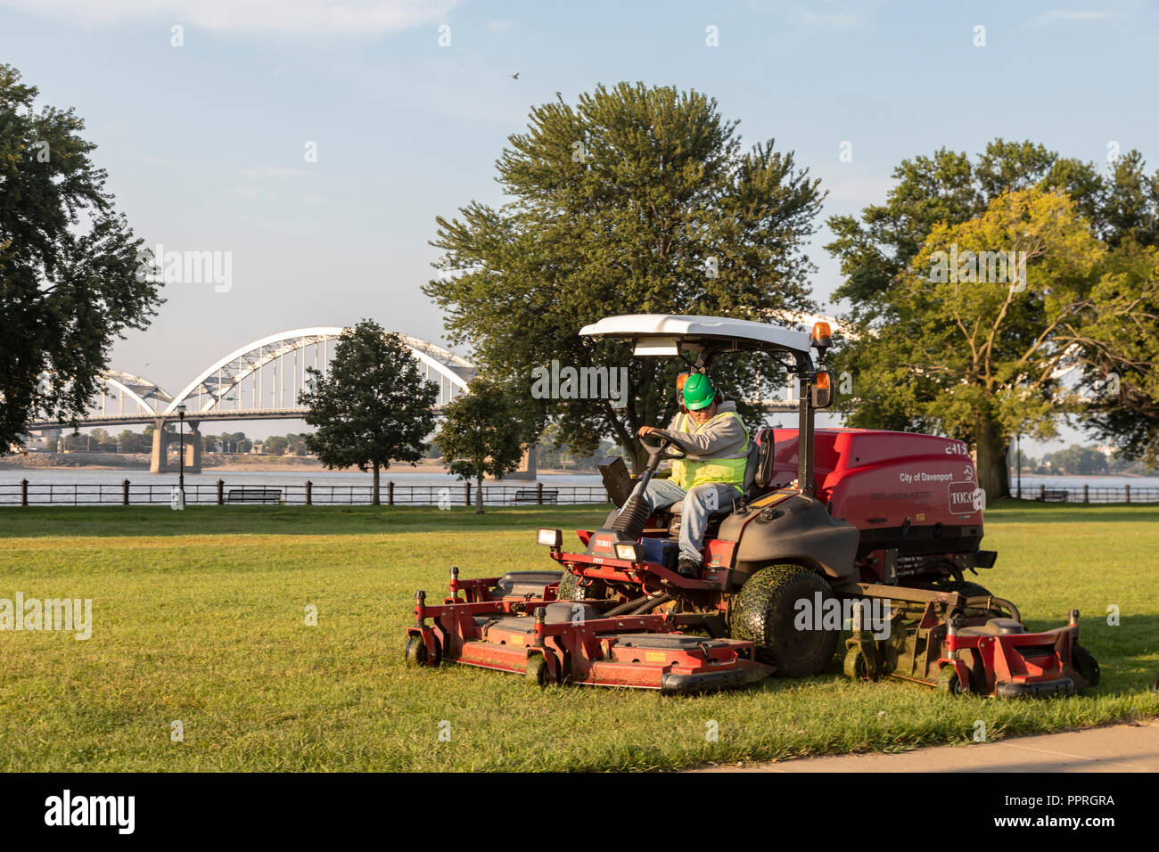 Davenport, Iowa - A city employee cuts the grass in LeClaire Park, along the Mississippi River. - Stock Image