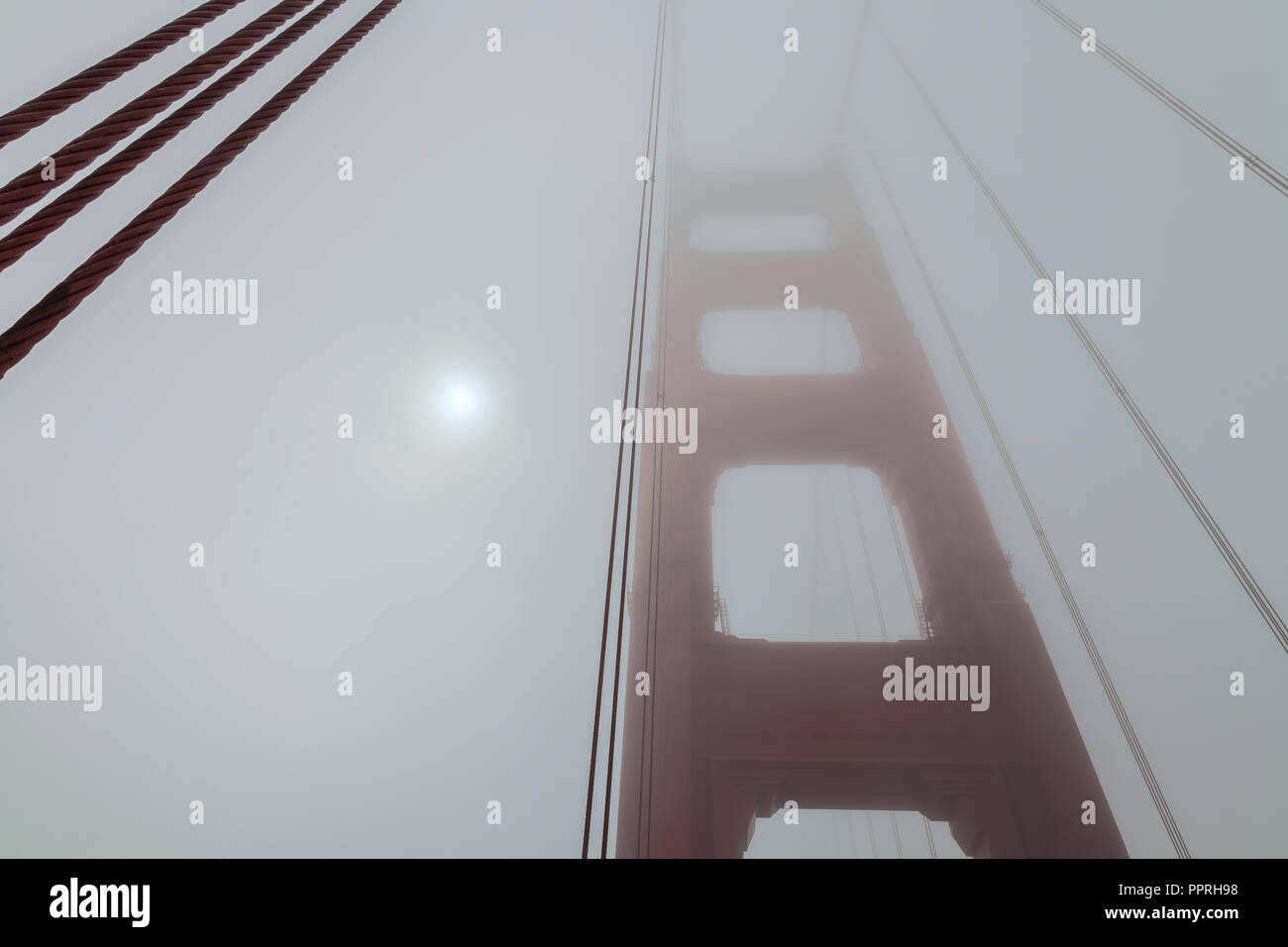 Morning sun is shining through the thick fog at the Golden Gate Bridge on a  late summer day, San Francisco, California, United States - Stock Image