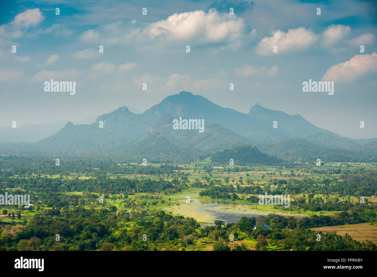 View to distant mountain range from the top of Sigiriya Rock. Green hazy landscape with blue cloudy sky background - Stock Image