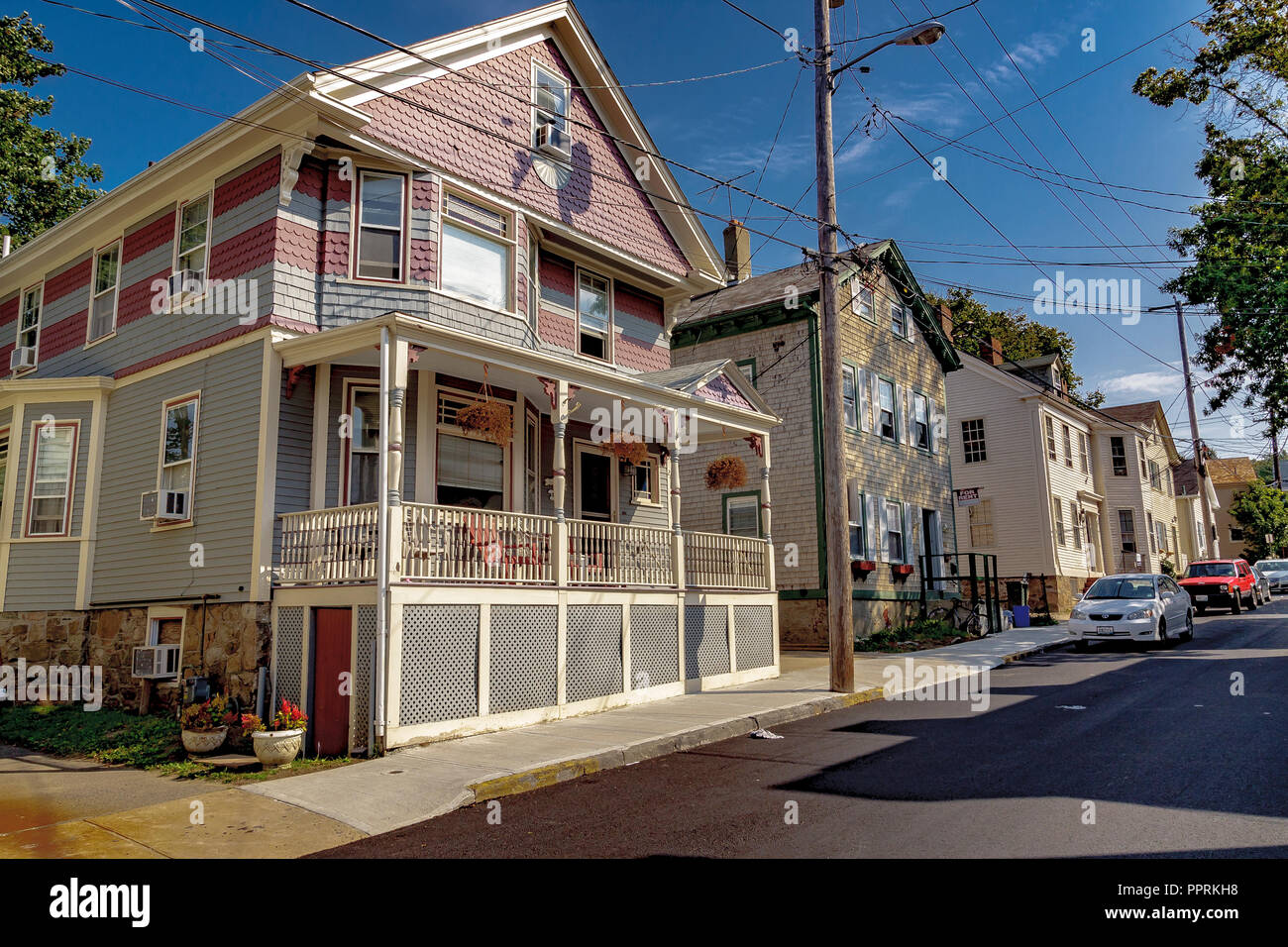 Wooden clap board house with front porch and veranda ,with pink and grey tile cladding on the upper level ,Howard St,Newport Rhode Island,USA - Stock Image