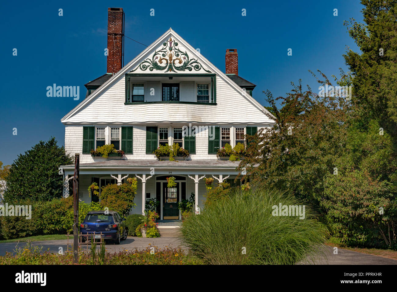 White wooden house with green shutters and a balcony built into the gable complete with design on the front gable, Kay St ,Newport Rhode Island, USA - Stock Image
