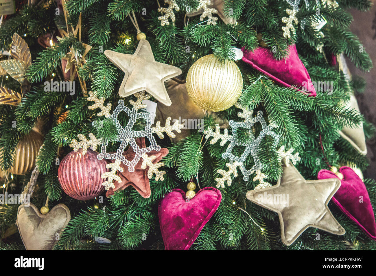 Different decorative Christmas-tree toys close-up, decorations for Christmas tree, green spruce branch needles. Winter Christmas New Year background. - Stock Image