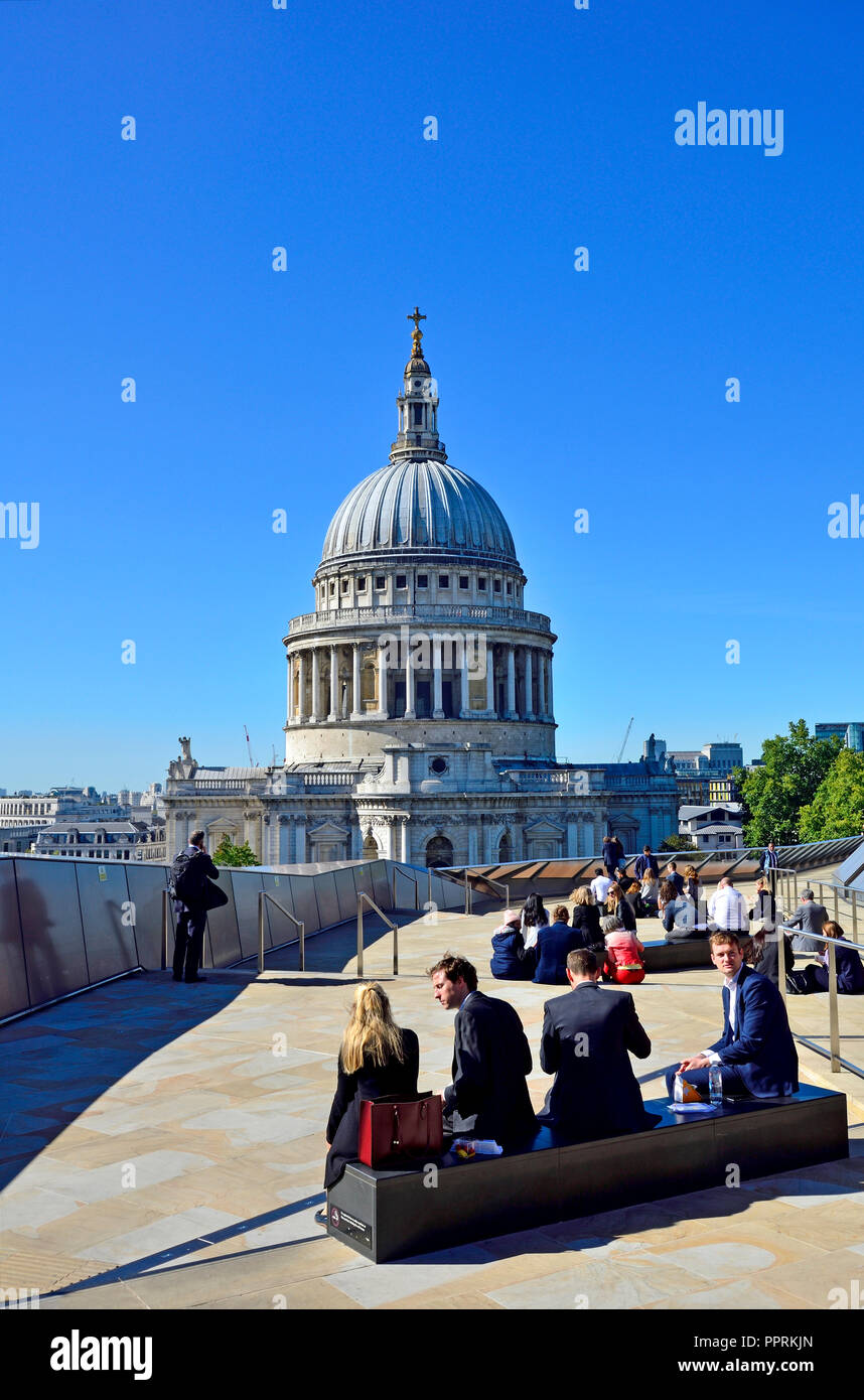 Office workers eating lunch on the roof of One New Change with a view of St Paul's Cathedral, London, England, UK. - Stock Image