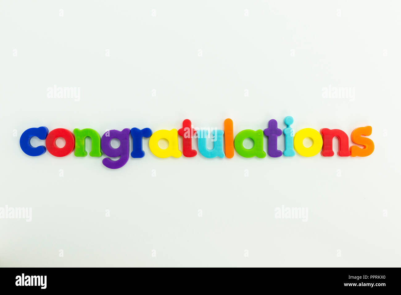 Congratulations spelled out with colourful children's fridge magnets - Stock Image
