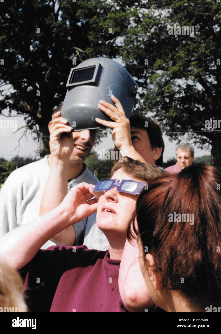 Eye protection -  August 1999. A Total Solar Eclipse is imminent in Hampshire UK and all means of eye protection, including a welder's mask, are used. - Stock Image