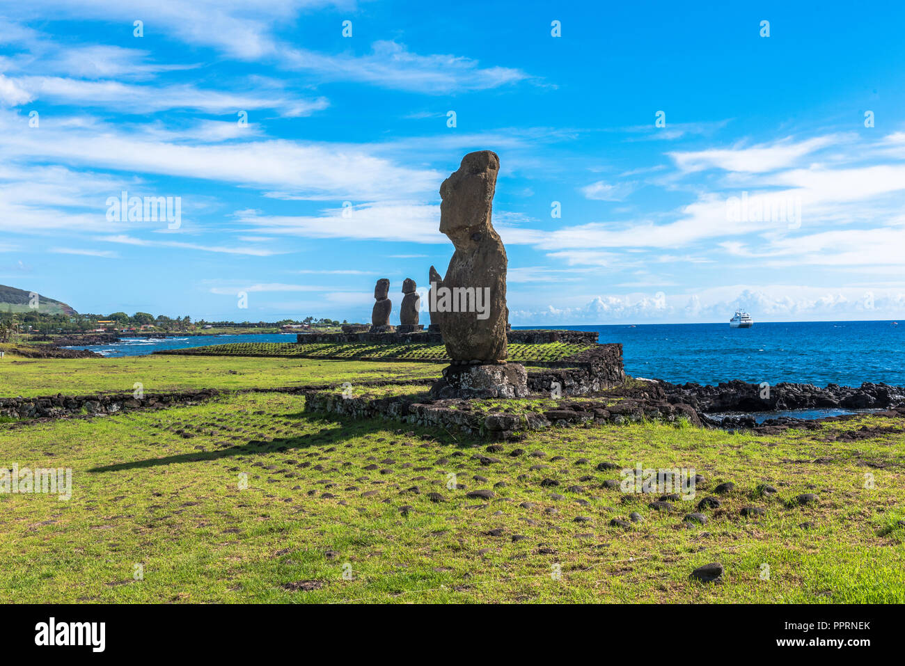 A row of Moai statues on the coast looking inward onto Easter Island. under a bright blue sky. - Stock Image