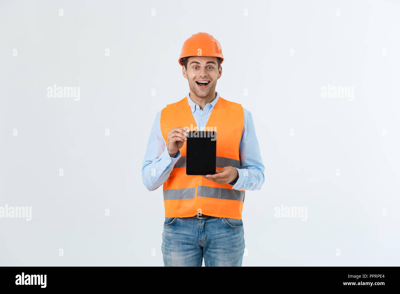 Shocked male engineer showing tablet screen, looks with opened mouth as remembers about important meeting. Male in stressful situation. Surprise and shock concept - Stock Image