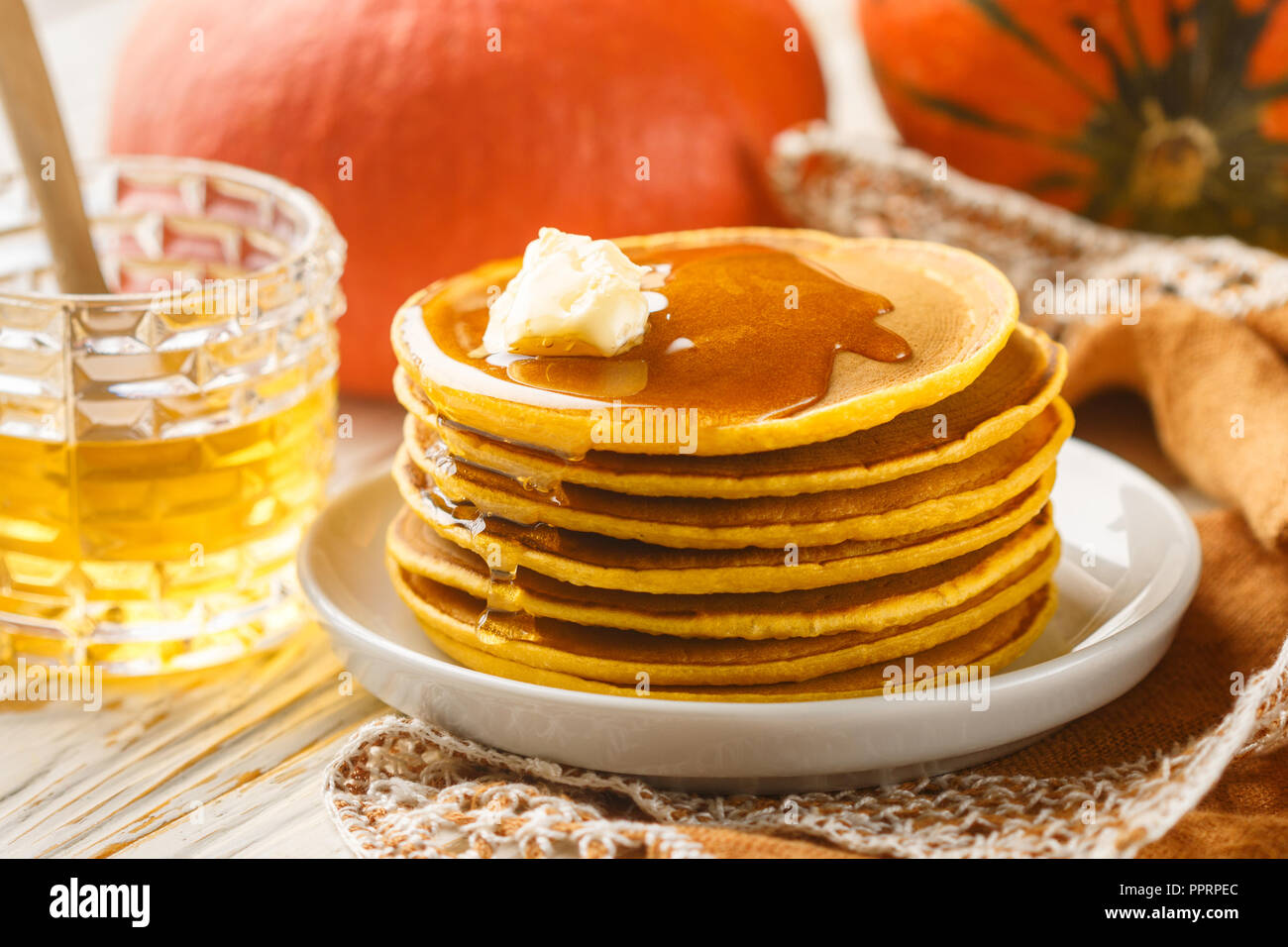Fresh homemade pumpkin pancake with honey and butter in a white plate. Traditional Tasty healthy Breakfast for gourmets. Selective focus Stock Photo