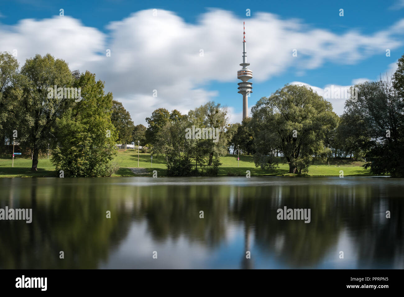 Munich Olympic Tower long exposure with the lake in the foreground. - Stock Image