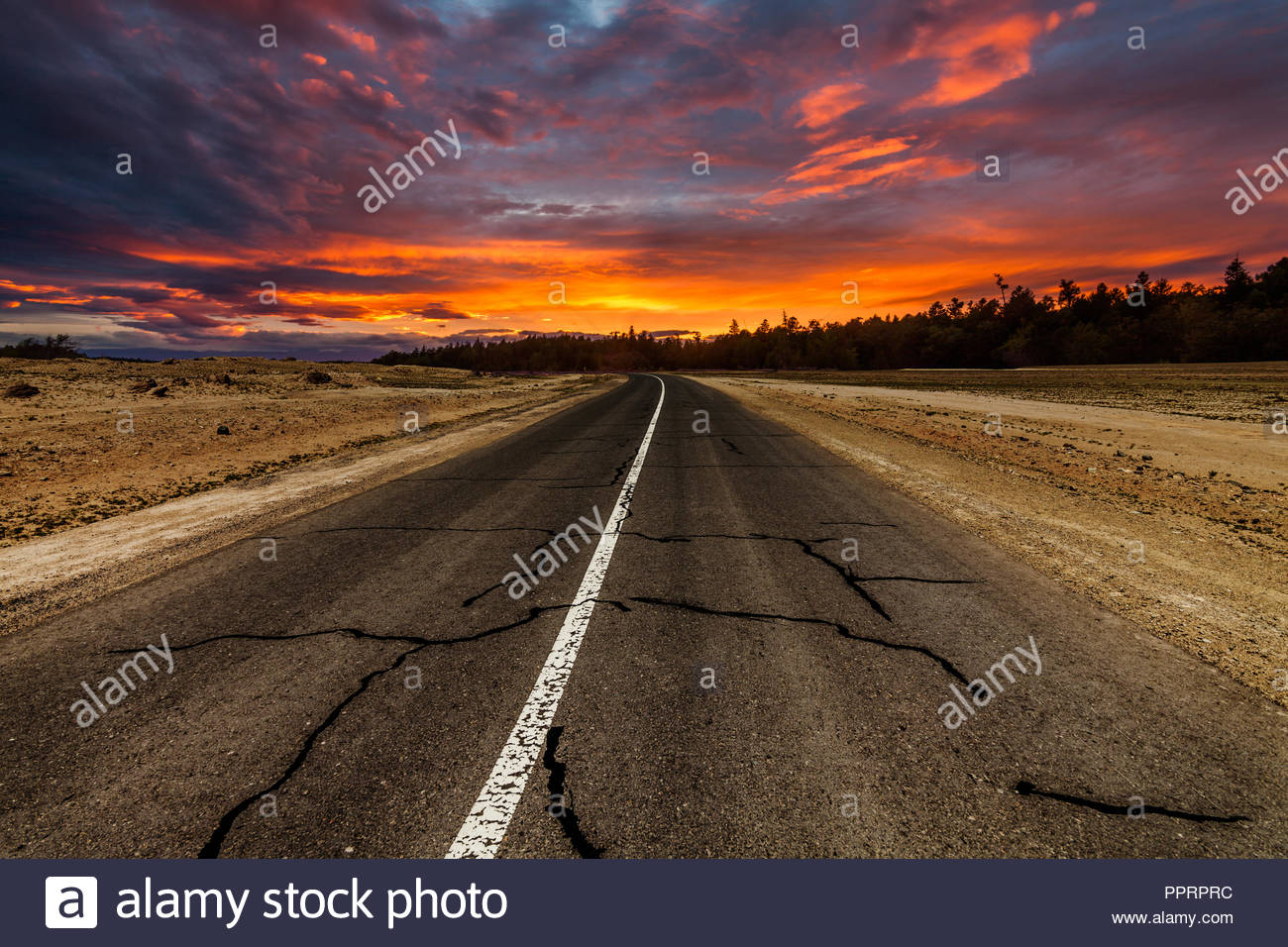 Picturesque fiery sunset over the cracked desert road - Stock Image