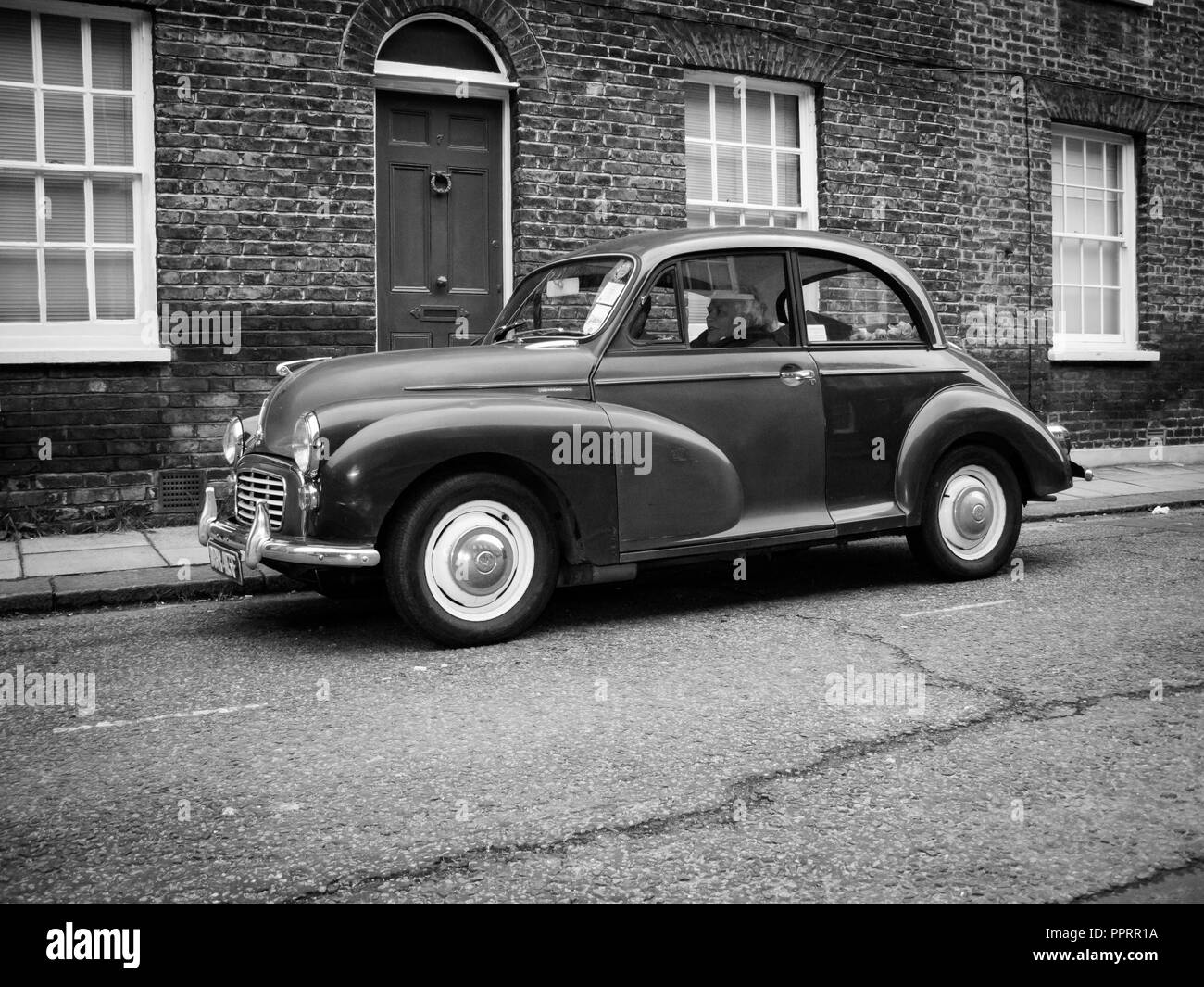 Morris Minor parked in front of a row of terraced houses in London. - Stock Image