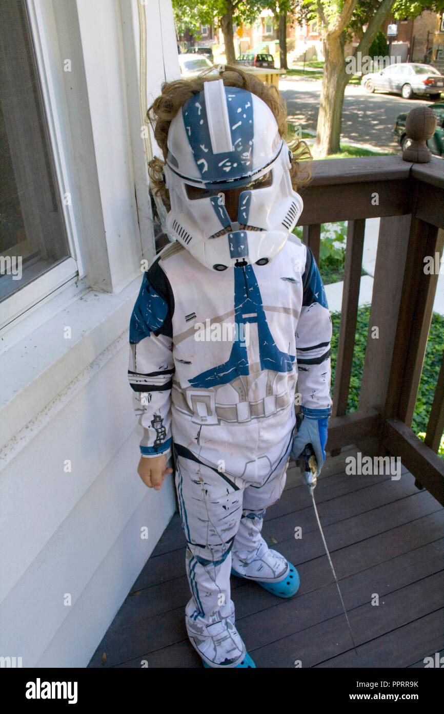 Young boy on his front porch defending his home in a Star Wars Clone Trooper costume holding a light saber. Chicago Illinois IL USA - Stock Image