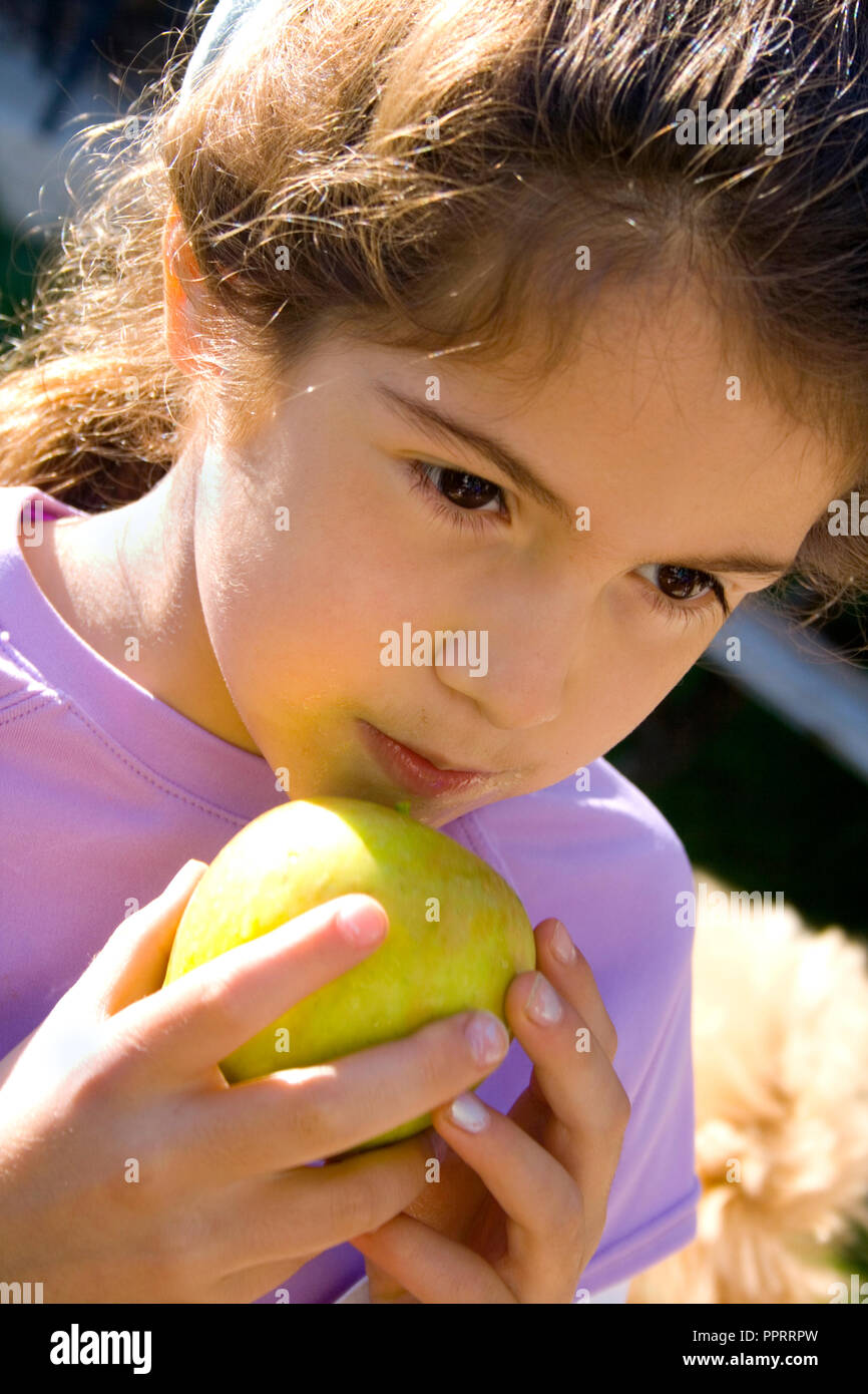 Young thoughtful girl age 8 ready to take a bite out of an apple. St Paul Minnesota MN USA - Stock Image