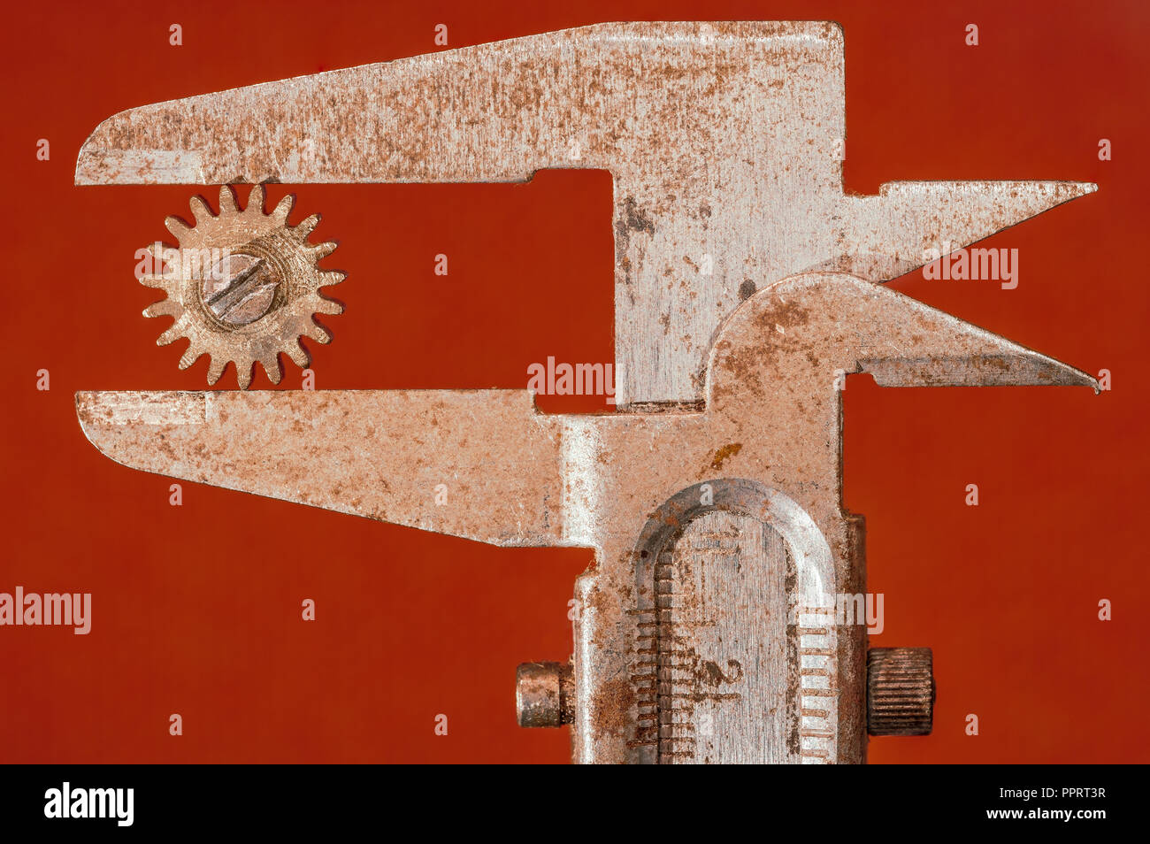 Diameter of a cogwheel is measured with a rusty caliper. - Stock Image
