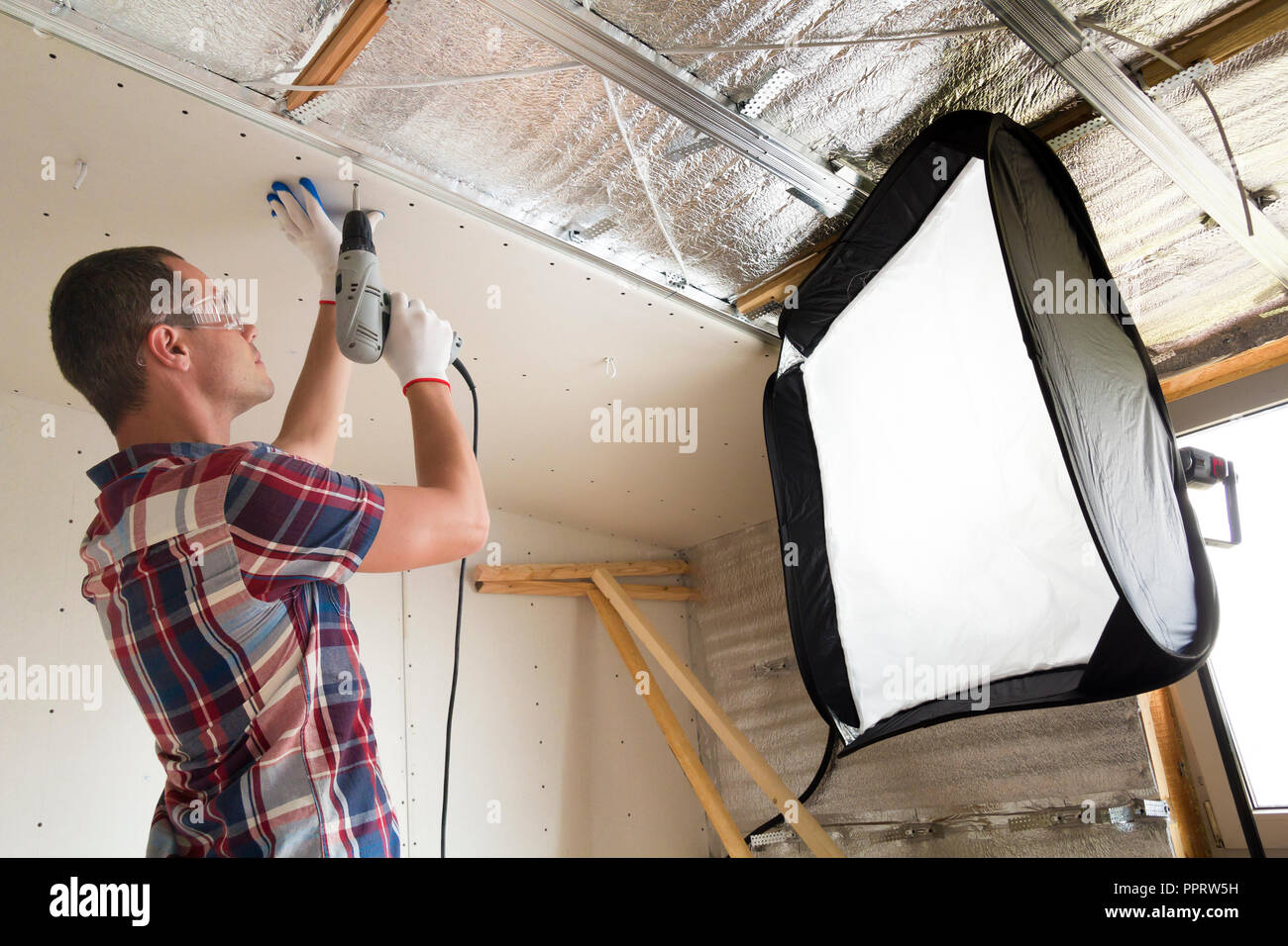 Young man in goggles and work gloves fixing drywall