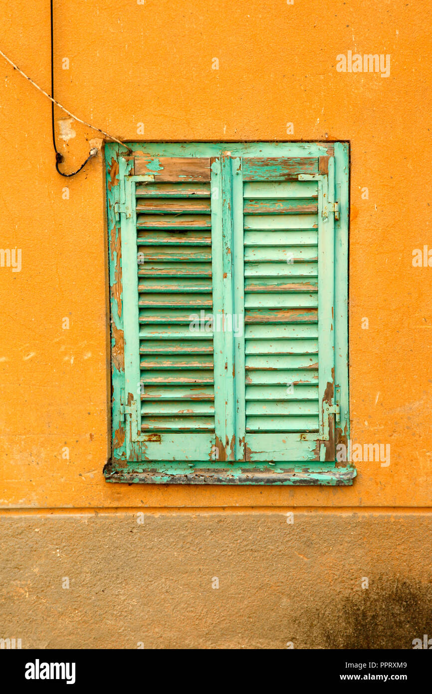 A Rustic Wooden Shutter In Mint Green On A House In The