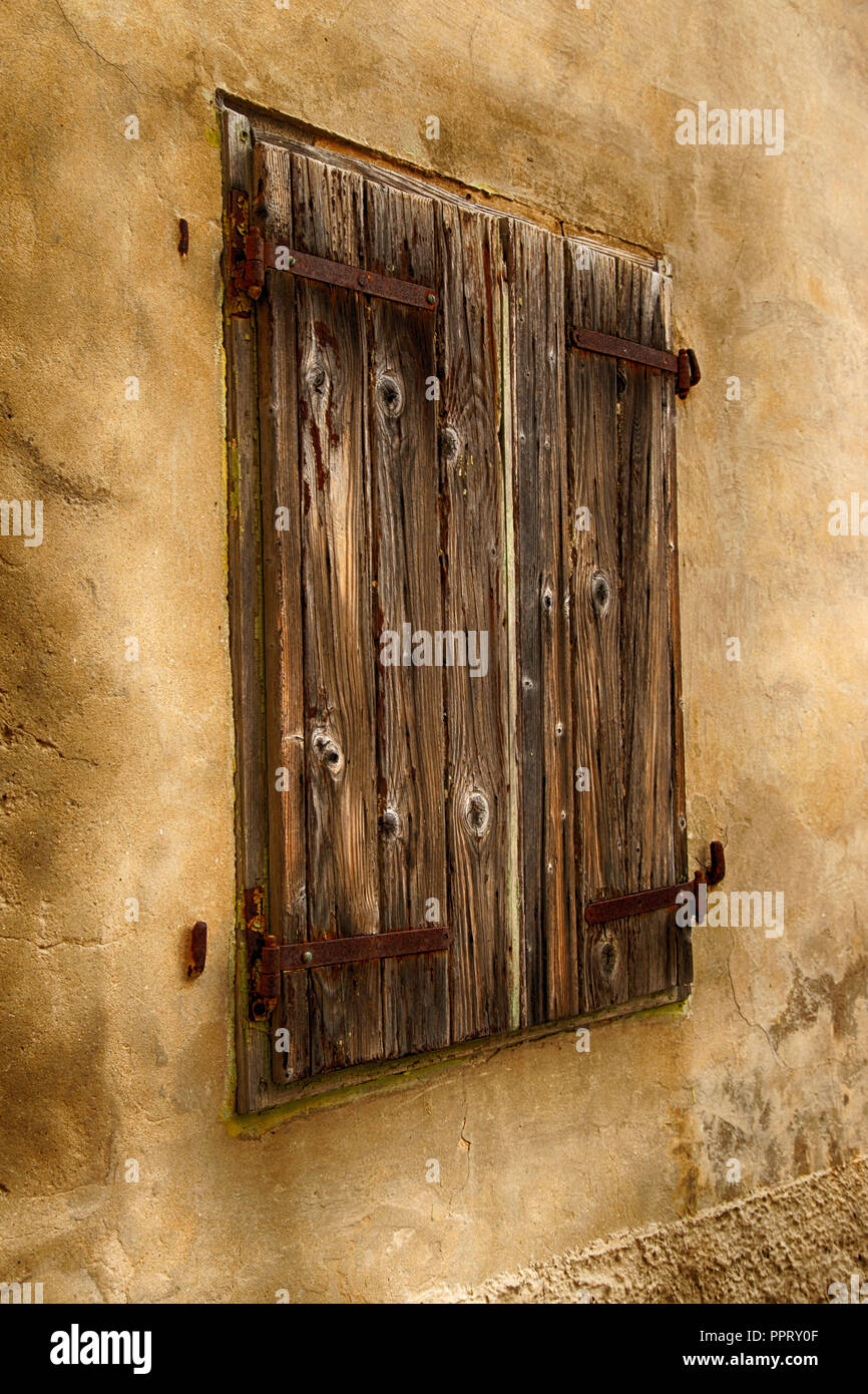 Large closed wooden shutters on a medieval building on the interwoven labyrinths of stone alleys in village of Vrbnik on the Croatian island of Krk - Stock Image