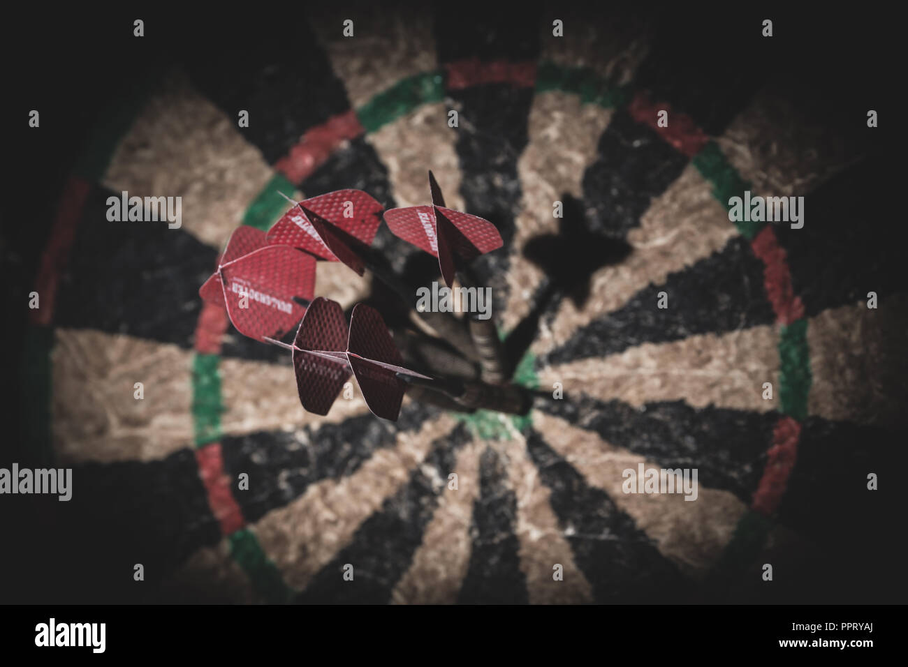 Some darts stuck in the bullseye of a cheap dartboard. - Stock Image