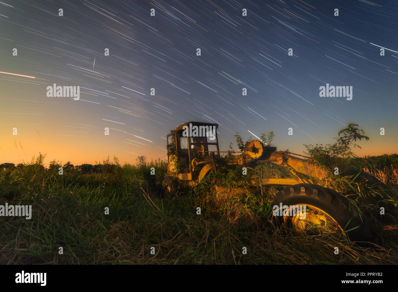 An old Caterpillar Road Grader rusts away in a pasture while star trails and a satellite streak overhead. Stock Photo