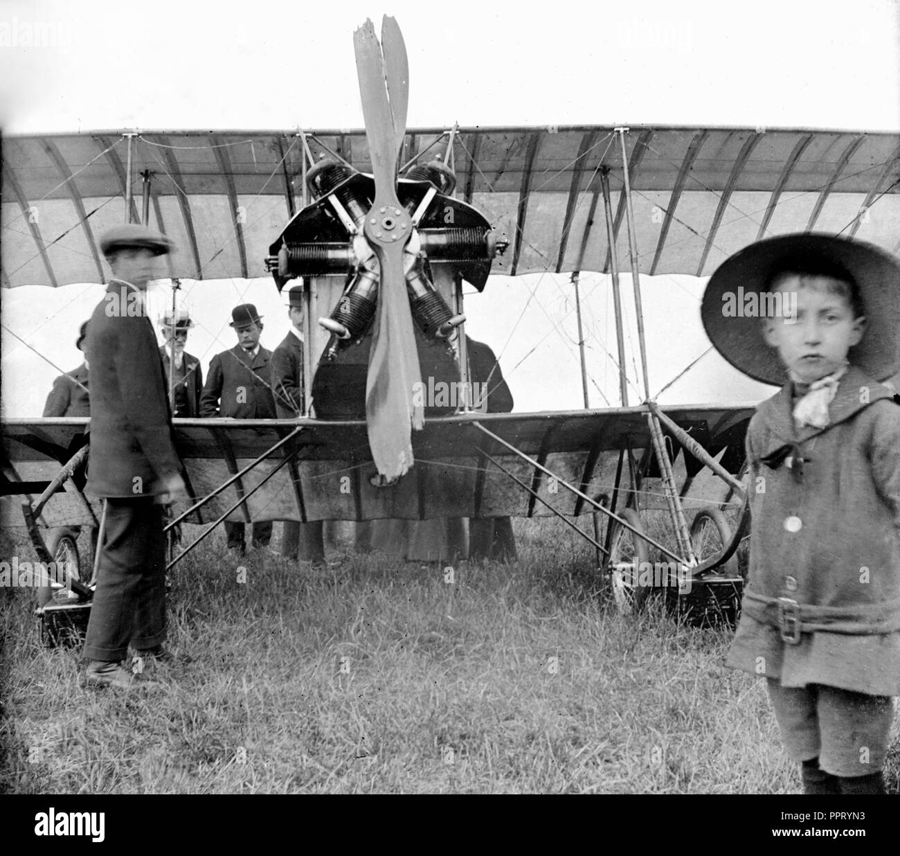 A group of men and boys look over an airplane that crash landed outside London, ca. 1914. - Stock Image