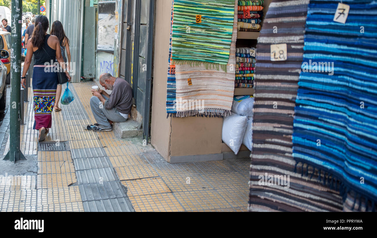 Athens Greece/August 17, 2018: Woman walking down closed down flea market with graffiti on the closed doors Stock Photo