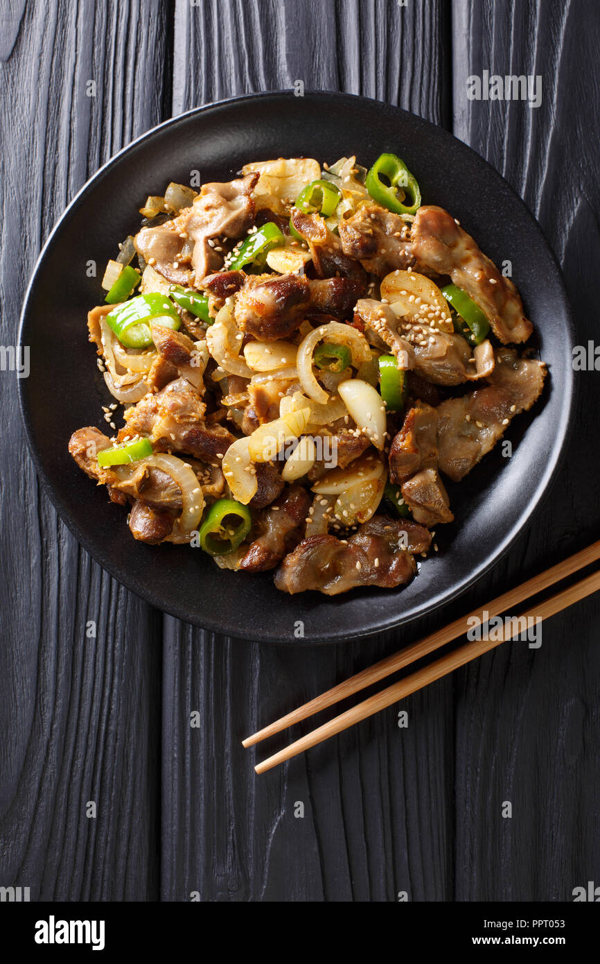 Dak Ddong Jjip - Fried chicken stomachs with onions, garlic, chili and sesame close-up on the table. Vertical top view from above - Stock Image