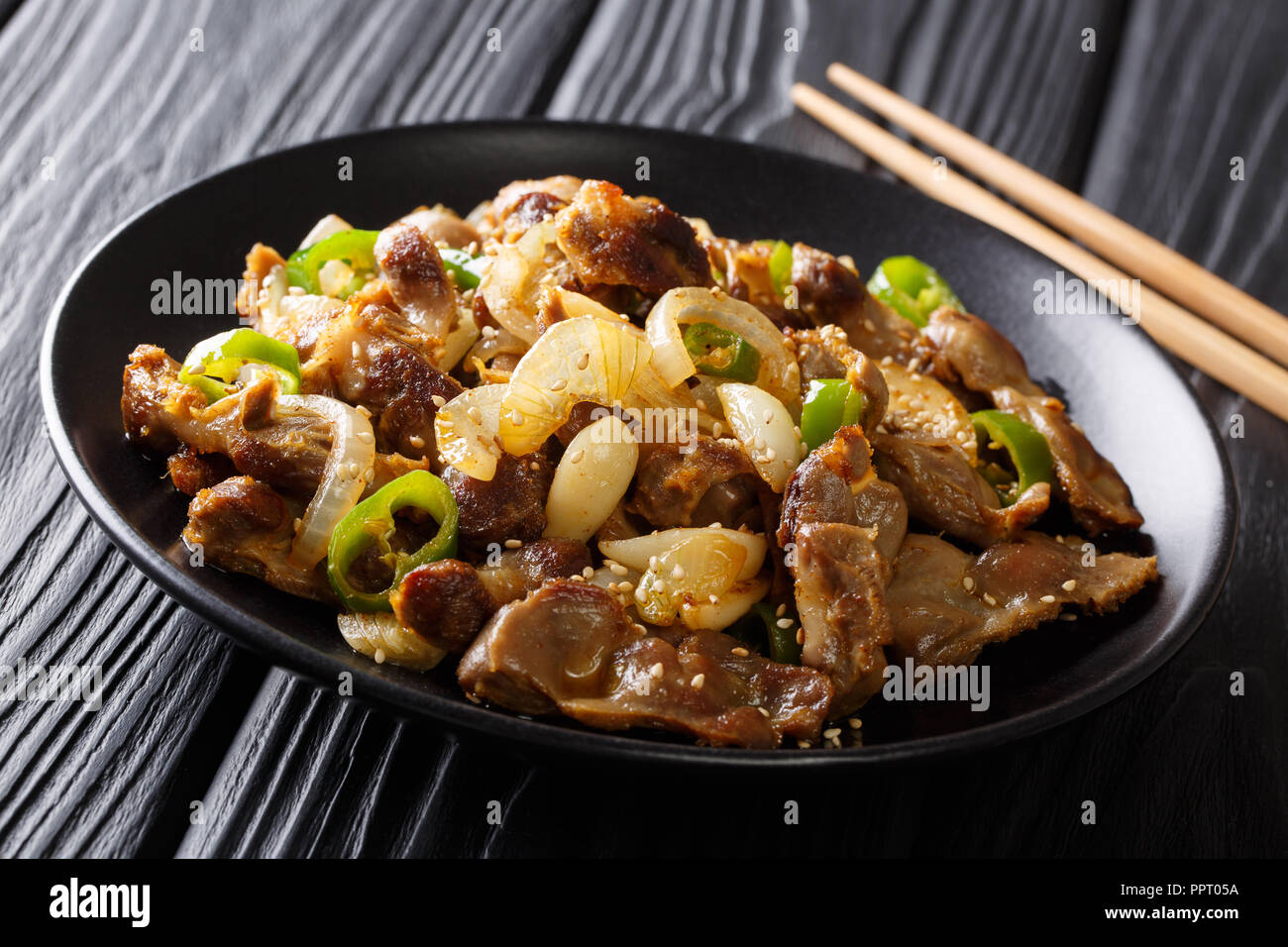 Asian food: spicy chicken stomachs with jalapeno pepper, onion, garlic and sesame close-up on a plate. horizontal - Stock Image