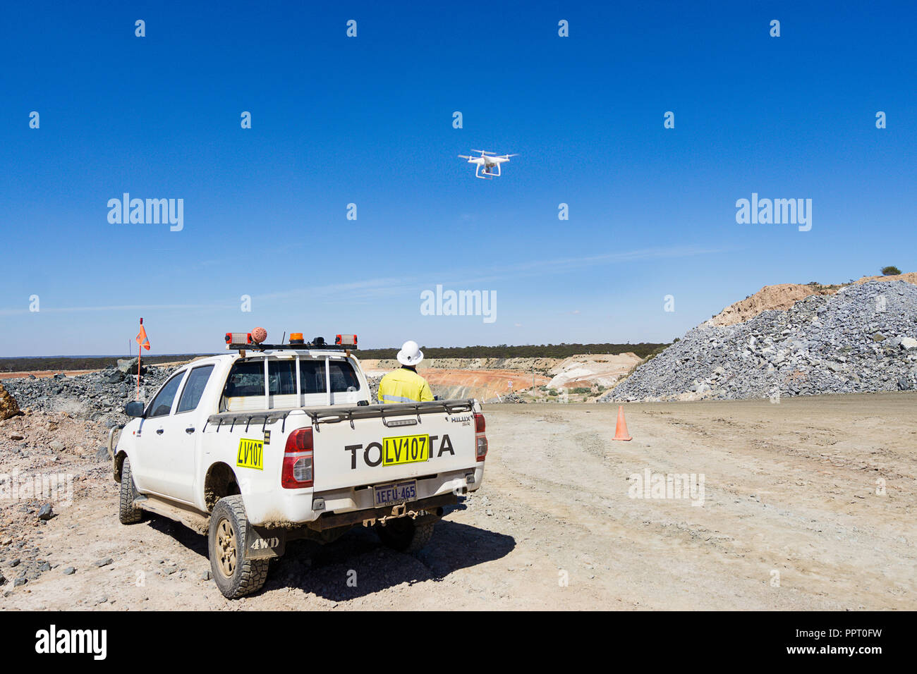 Surveyor using a drone to measure ore stockpile at a gold mine in Western Australia Stock Photo