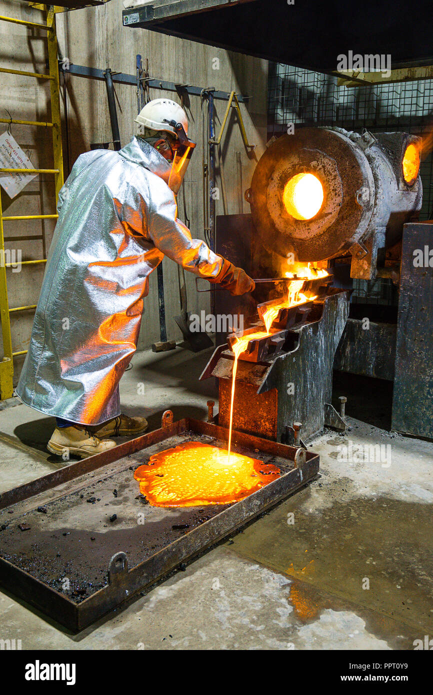 Worker in protective clothing pouring gold from a furnace at a gold mine in Western Australia Stock Photo