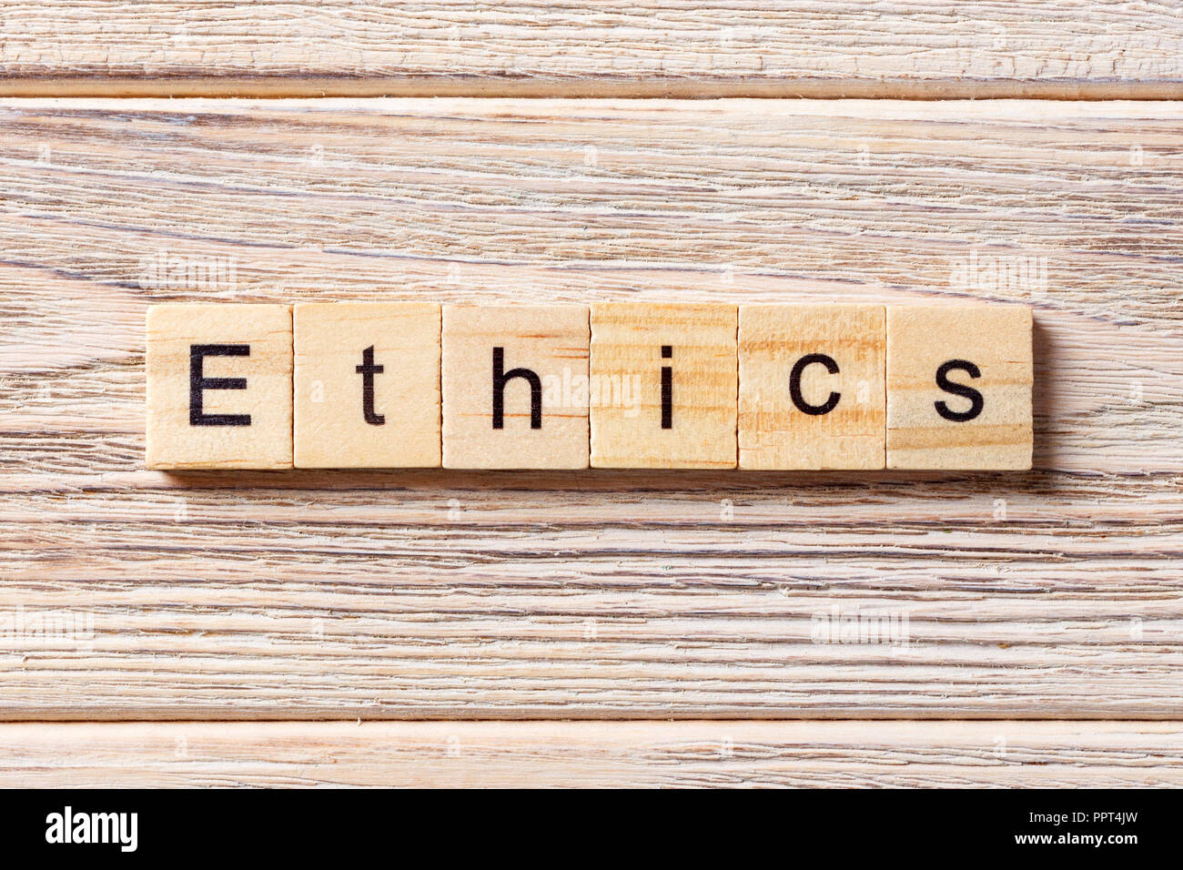 Ethics word written on wood block. Ethics text on table, concept. - Stock Image