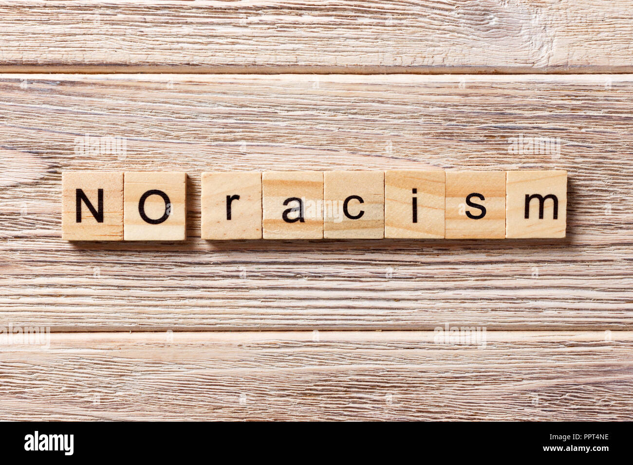 No racism word written on wood block. No racism text on table, concept. - Stock Image