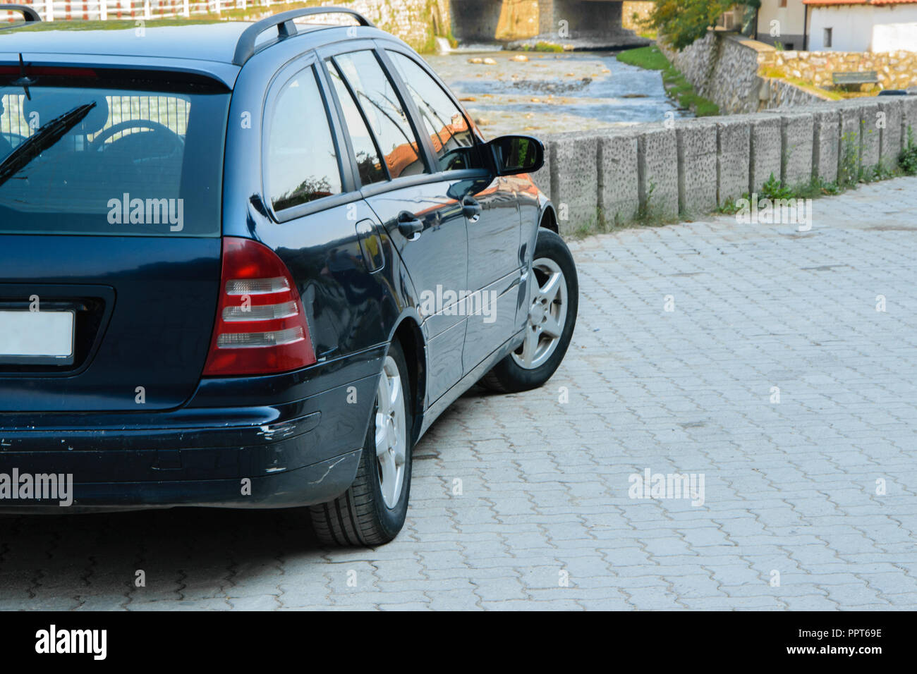 Family car parked a few centimeters from the wall of the river bridge, copy space. Concepts - accident, dangerous driving, insurance - Stock Image