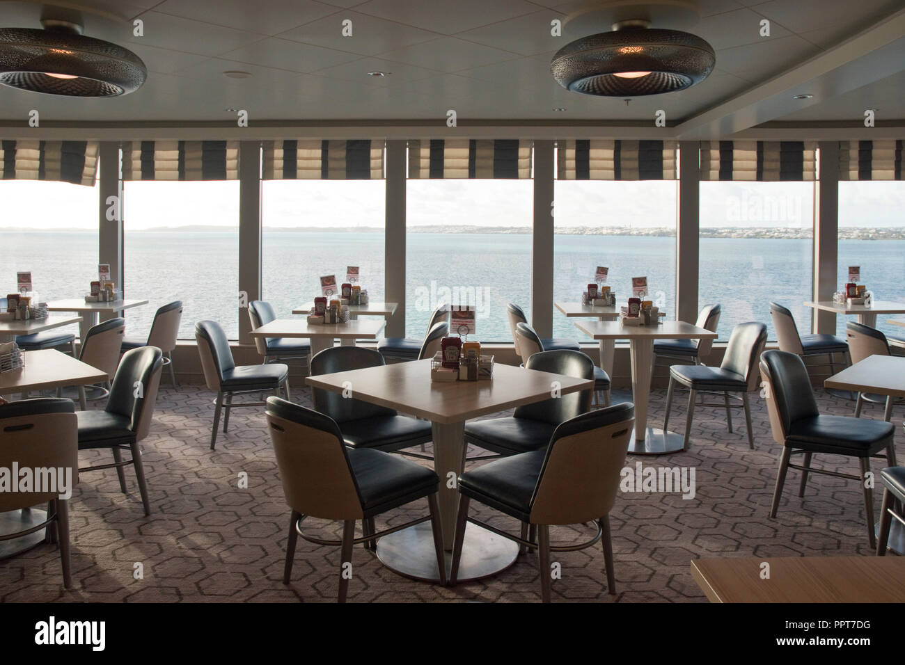 Tables and chairs in the cafeteria of the Norwegian Breakaway cruise ship at Bermuda. - Stock Image