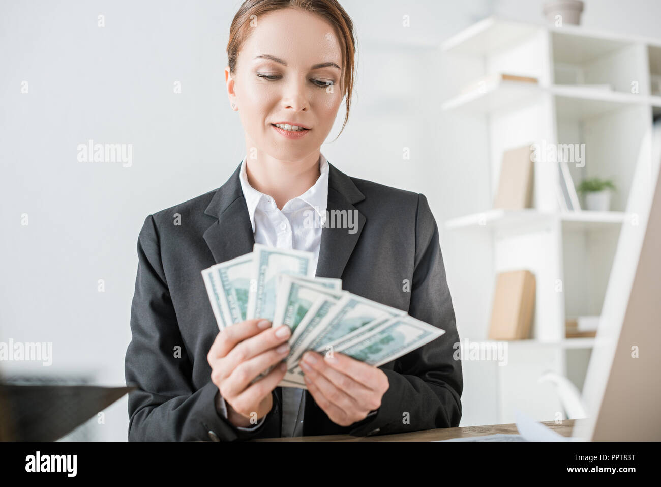 smiling financier counting cash in office - Stock Image