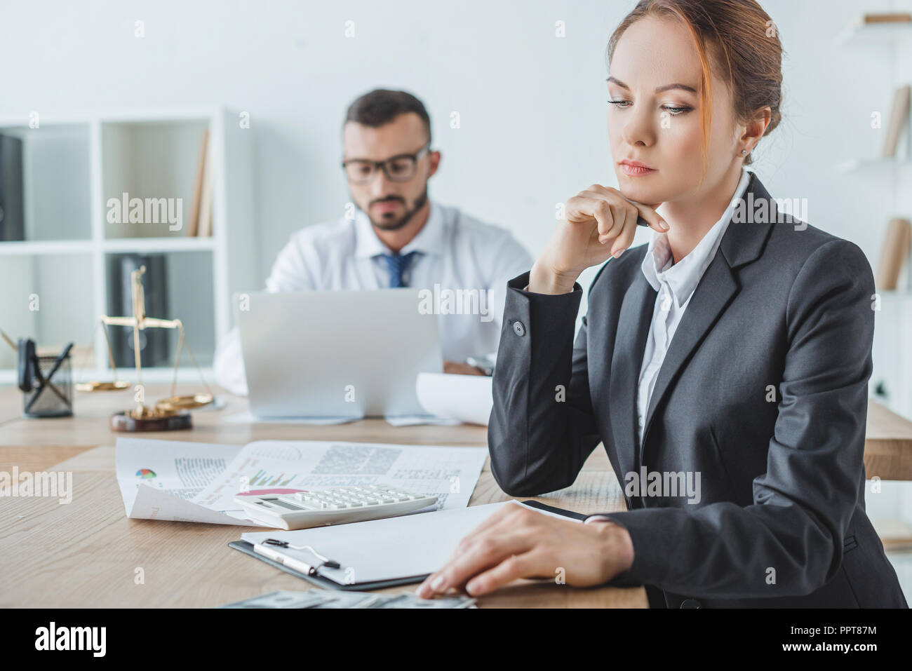 accountants working in office with documents and laptop - Stock Image
