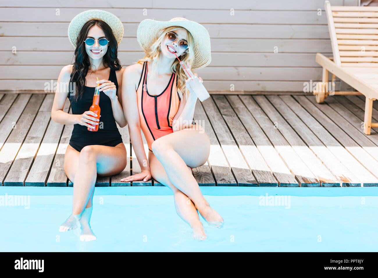beautiful young women in swimwear drinking summer beverages and smiling at camera near pool - Stock Image